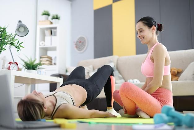 Trener nauczania młodych kobiet sportowych treningu w mieszkaniu. koncepcja domu fitness