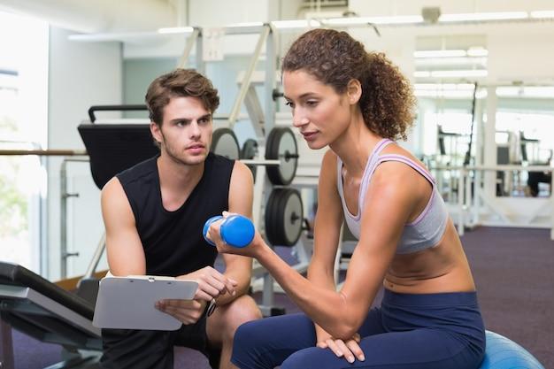 Trener ogląda klienta dźwignięcia dumbbells na ćwiczenie piłce