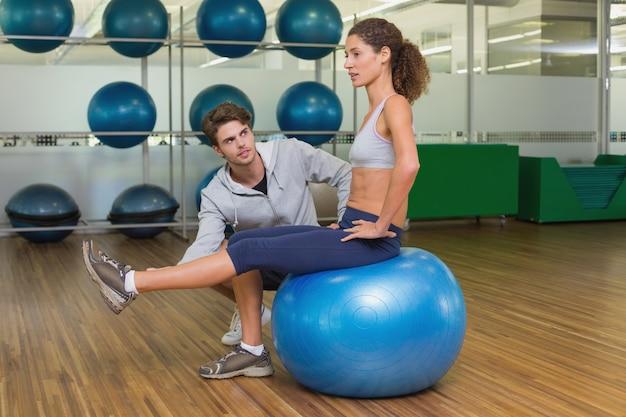 Trener ogląda swojego klienta za pomocą piłki do ćwiczeń