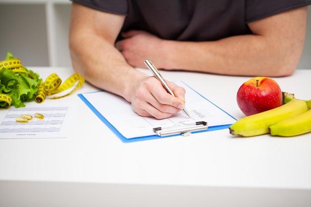 Trener opracowuje program treningowy i plan zdrowej diety