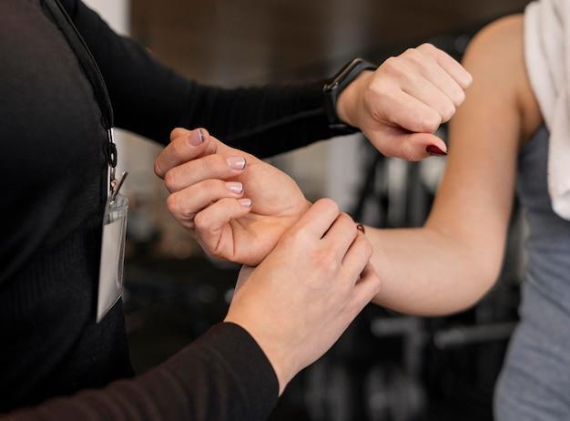Trener osobisty sprawdzający ramię klienta