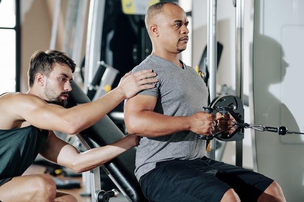 Trener personalny kontrolujący swojego klienta z wyprostowanymi plecami podczas ćwiczeń na maszynie rzędowej na siłowni