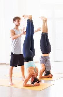 Trener personalny oferujący pomoc dwóm osobom wykonującym jogę na głowie na siłowni