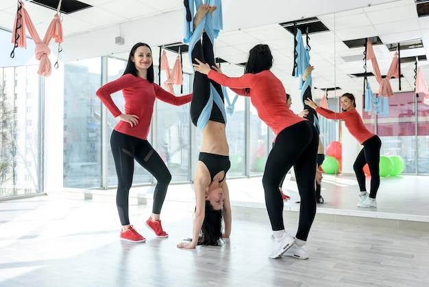 Trener personalny pomagający kobiecie rozgrzewać się do ćwiczeń fitness w jasnej siłowni. zdrowy tryb życia