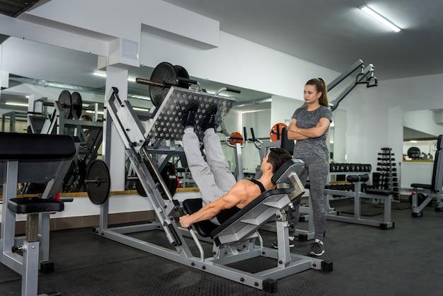 Trener personalny pomagający w pracy ze sztangą na siłowni