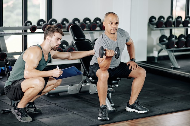 Trener personalny proszący dojrzałego klienta o trzymanie się wyprostowanych pleców podczas ćwiczeń bicepsów z hantlami na siłowni
