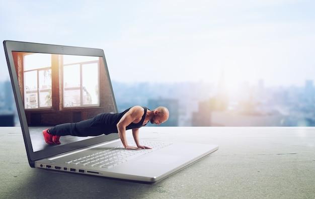 Trener personalny prowadzi zajęcia na siłowni przez internet i laptopa