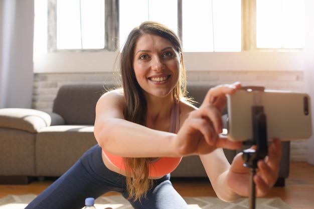 Trener personalny prowadzi zajęcia na siłowni przez smartfona
