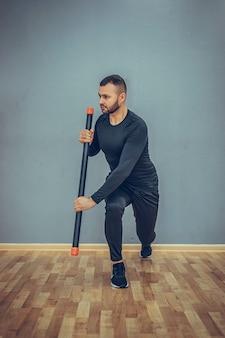 Trener personalny wykonujący ćwiczenia z fitbarem