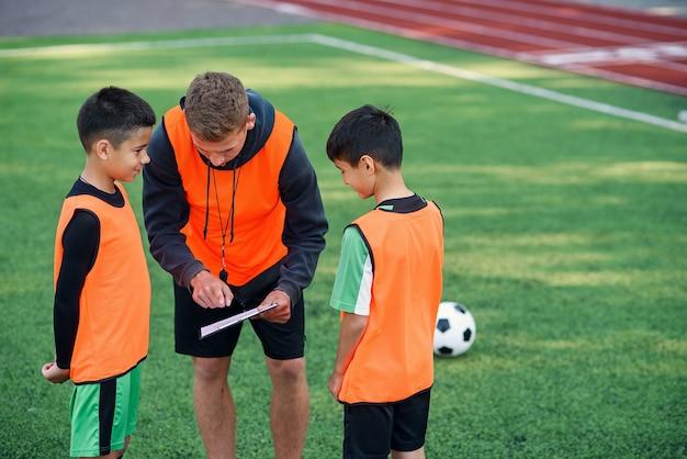 Trener piłkarski instruuje nastoletnich piłkarzy. młody profesjonalny trener wyjaśnia dzieciom strategię gry.