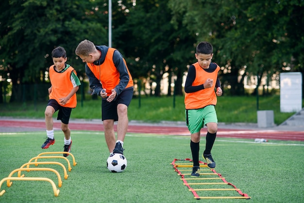 Trener piłki nożnej obserwuje swoich podopiecznych wykonujących ćwiczenia biegowe z pokonywaniem przeszkód