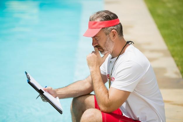 Trener pływania patrząc na schowek w pobliżu basenu