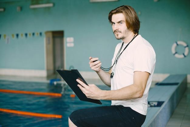 Trener pływania stojący przy basenie. sprawdzanie rekordów pływania. trzymając schowek.
