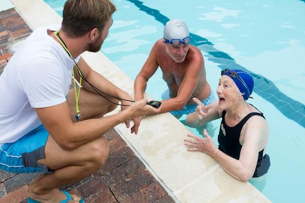 Trener pływania wchodzący w interakcję z parą seniorów przy basenie