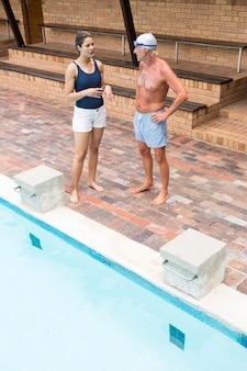 Trener pływania wchodzący w interakcję ze starszym mężczyzną przy basenie