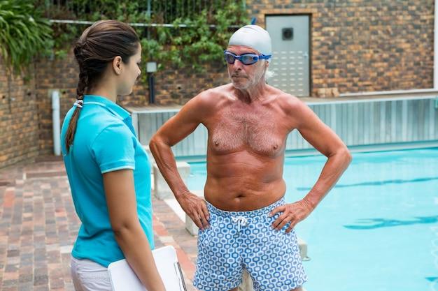 Trener pływania wchodzący w interakcję ze starszym mężczyzną w pobliżu basenu