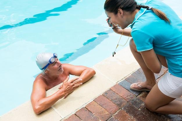 Trener pokazujący stoper starszy mężczyzna przy basenie