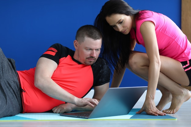 Trener pokazuje ćwiczenia uczniowi na laptopie.