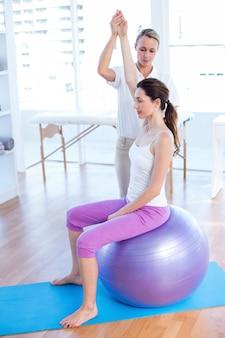 Trener pomaga kobieta na ćwiczenie piłce