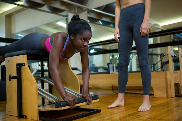 Trener pomaga kobieta z krzesłem wunda w studio fitness