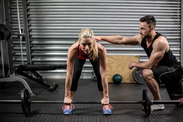 Trener pomaga kobieta z podnoszenia brzana w siłowni