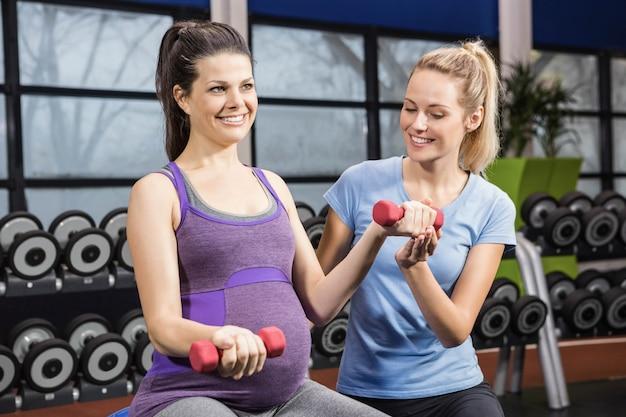 Trener pomaga kobiety w ciąży na siłowni z hantlami