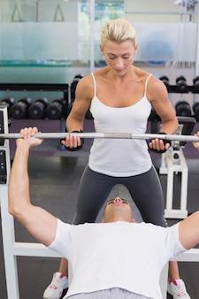 Trener pomaga mężczyzna z podnośnym barbell w gym