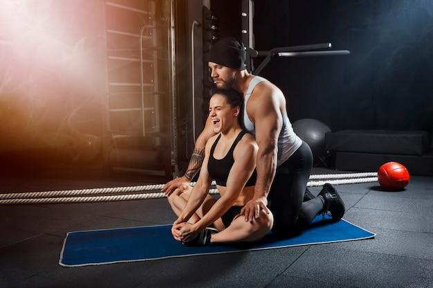 Trener pomaga sportowcowi rozciągnąć bolący staw.