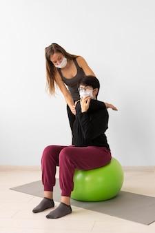 Trener pomagający kobiecie odzyskać siły po koronawirusie na piłce fitness