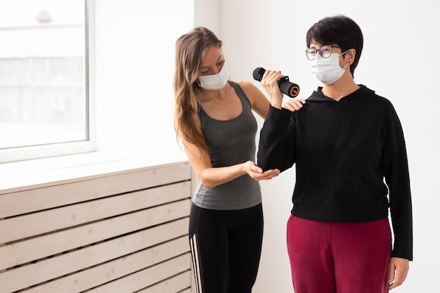 Trener pomagający kobiecie w rekonwalescencji po koronawirusie