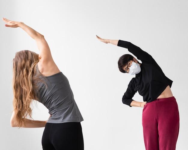Trener pomagający kobiecie wyleczyć się z choroby zakaźnej na siłowni