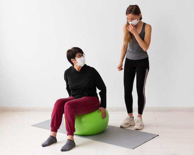 Trener pomagający kobiecie wyleczyć się z choroby zakaźnej podczas noszenia masek medycznych