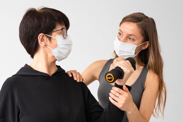 Trener pomagający kobiecie wyleczyć się z koronawirusa z ciężarami