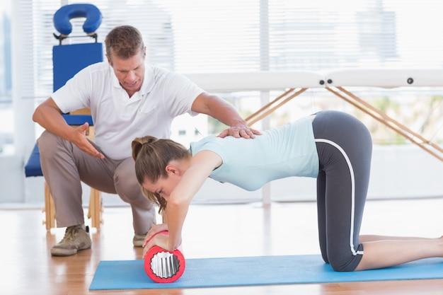 Trener pracuje z kobietą na matę do ćwiczeń