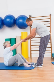 Trener pracuje z starszą kobietą na matę do ćwiczeń