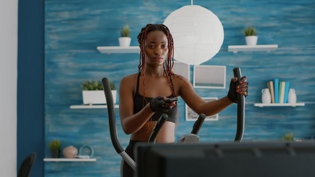 Trener slim fit noszący odzież sportową chodzący na rowerze eliptycznym oglądając rutynę aerobową
