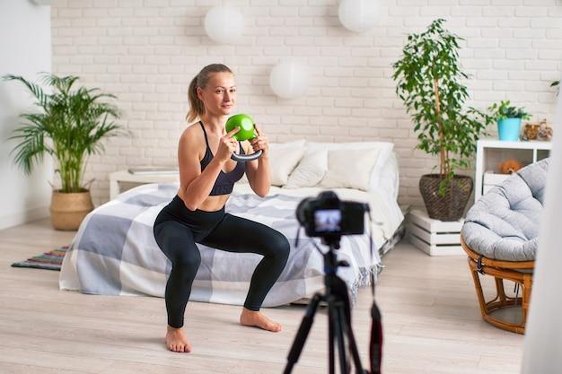 Trener strumieniowy online pokazuje technikę wykonywania ćwiczeń z ciężarami. trening mięśni nóg.
