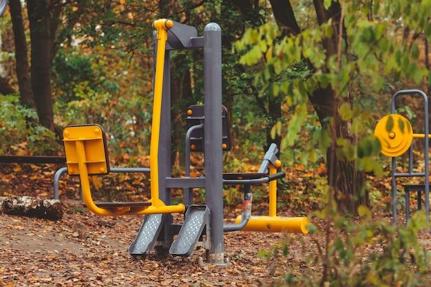 Trener symulatorów kulturystyki na zewnątrz w jesiennym parku miejskim