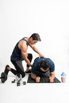 Trener towarzyszy mężczyźnie wykonującemu ćwiczenia deski, powstrzymując się przed wykonaniem odpowiednich ruchów