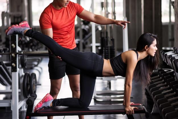 Trener trener rozciągania nogi do dziewczyny w siłowni