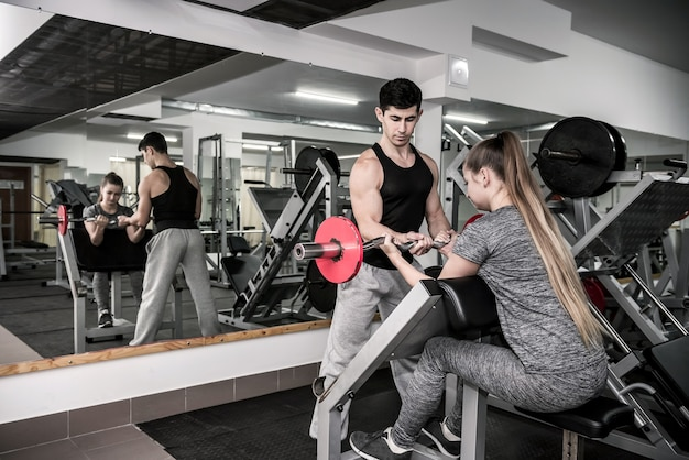 Trener trenowania młodej i pięknej kobiety w siłowni