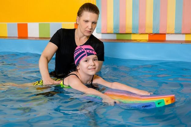 Trener uczy dzieciaka w krytym basenie, jak pływać i nurkować. koncepcja szkolenia