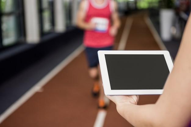Trener używa cyfrową pastylkę podczas gdy mężczyzna wykonuje bieg ćwiczenie