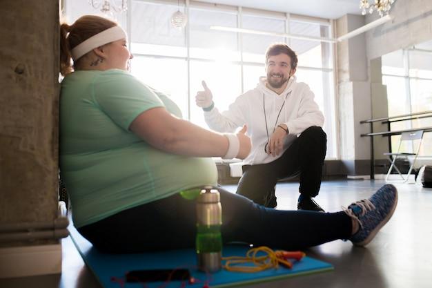 Trener wspierający otyłą kobietę