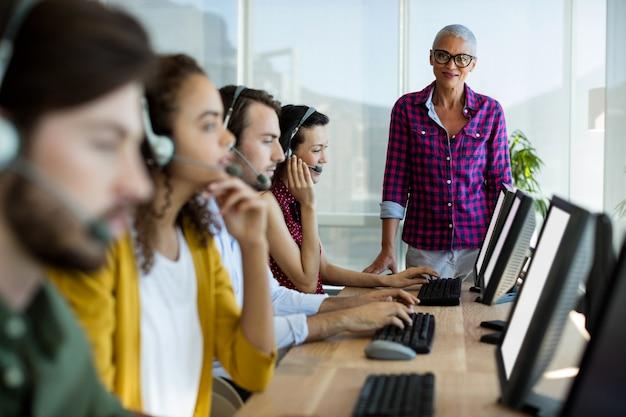 Trener wykonawczy ds. obsługi klienta monitorujący swój zespół w biurze