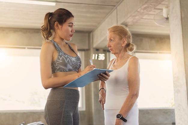 Trener z starszą kobietą w centrum rehabilitacji.