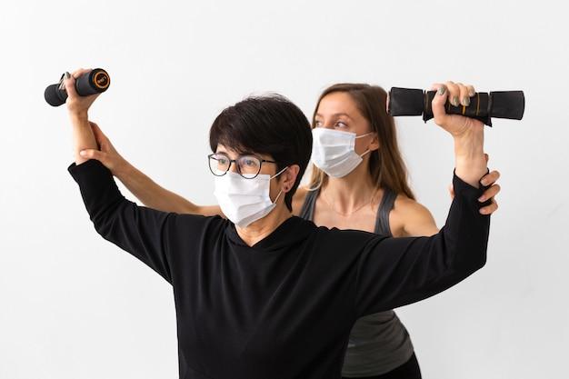 Trener z widokiem z przodu pomaga kobiecie odzyskać zdrowie po koronawirusie