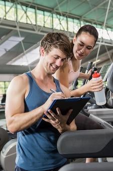 Trenera writing na schowku podczas gdy kobieta ćwiczy na eliptycznej maszynie