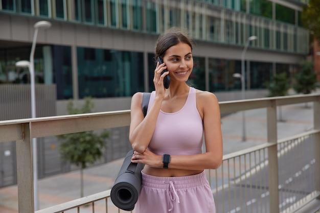 Trenerka jogi szczęśliwy rozmawia telefonicznie prowadzi matę gimnastyczną w drodze do studia fitness. sportsmenka w odzieży sportowej wraca z pilatesu czuje się wypoczęta i pełna energii stoi na świeżym powietrzu
