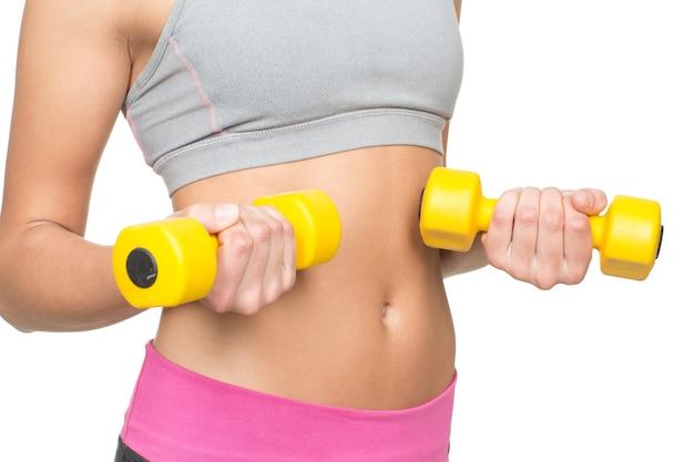 Trening bicepsów. przycięte studio strzał zdrowej kobiety sprawny, trzymając hantle w pobliżu brzucha